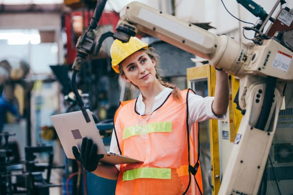 Female worker working with laptop at robotic factory
